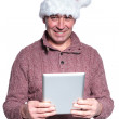 Senior casual man wearing santa hat is holding a pad tablet — Stock Photo