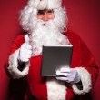 Santa claus is reading about good news on his tablet pad — Stock Photo