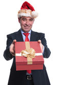 Business man in santa hat offering a present box — Stock Photo