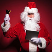 Santa claus is ringing his bell while reading on tablet — Stock Photo