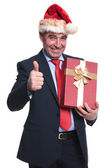 Business man santa holds present and makes ok sign — Stock Photo