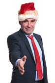 Business man in christmas hat welcomes you with a hand shake — Stock fotografie