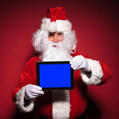 Santa claus is showing a blank screen of his tablet pad — Stock Photo