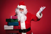 Santa claus is inviting you to get some presents — Stock Photo