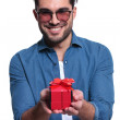 Smiling young man is offering a red gift box — Stock Photo