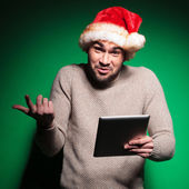Undecided young santa man holding a tablet pad — Stock Photo