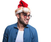 Side smilling man wearing santa hat looking away — Stock Photo