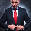 Serious old business munbuttoning his suit — Stock Photo #38601331