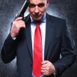 Smiling old killer holding his gun and pulling his suit — Stock Photo #38601347