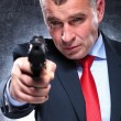 Old killer in suit and tie pointing his gun — Stock Photo #38601359