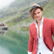 Young smiling man with a mountain lake in his back — Stock Photo #38601565