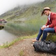 Man is resting near a mountain lake with cabin — Stock Photo