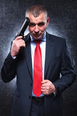 Smiling old killer holding his gun and pulling his suit — Stock Photo