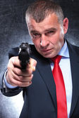 Old killer in suit and tie pointing his gun — Stock Photo