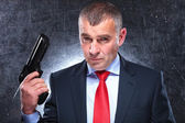 Dramatic picture of an old assassin holding his gun — Stock Photo