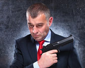 Pensive old assassin holding his gun — Stock Photo