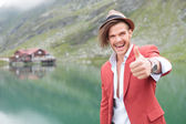Excited man making the ok gesture near lake — Stock Photo
