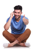 Seated man talking on phone and making ok — Stock Photo