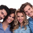 Foto Stock: Closeup picture of four casual young people smiling