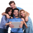 Four laughing casual people reading on tablet pad computer — Foto Stock #39037247