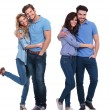 Stock Photo: Two happy couples of young casual people standing embraced
