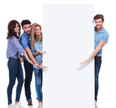 Casual friends pointing and showing you a blank banner — Stock Photo