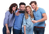 Smiling man taking a photo of his friends with phone — Stock Photo