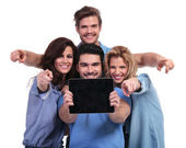 Group of people showing screen of tablet and point fingers — Stock Photo