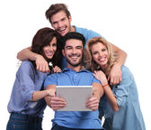 Four laughing casual people reading on a tablet pad computer — Stock Photo