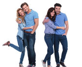 Two happy couples of young casual people standing embraced — Stock Photo