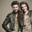 Stock Photo: Happy fashion couple in leather jackets smiling
