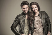 Happy fashion couple in leather jackets smiling — Stock Photo