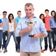 Old casual man holding a trophy cup in front of winning team — Stock Photo #39613019