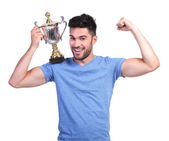 Man flexing his muscle and holding a trophy cup — Stok fotoğraf