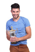 Portrait of a smiling casual man holding a trophy — Photo