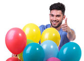 Happy man behind a baloons bunch making ok — Stock Photo