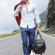 Young man walking with bag on the road — Stock Photo #41468951