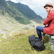 Постер, плакат: Young man sits on rock with his bag