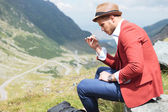 Young fashion man smokes in nature — Stock Photo