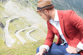 Outdoor fashion man sits and looks down — Stockfoto