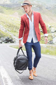 Young man walks with bag on road — Stock Photo