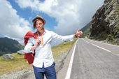 Young fashion man hitchhikes — Stock Photo