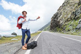 Young fashion man hitchhikes with joy — Stock Photo