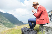 Young man lights cigarette in mountains — Stock Photo