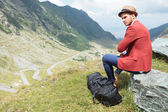 Young man sits on rock with his bag — Stok fotoğraf