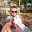 Man in a hammock in a resort pointing his finger — Stock Photo