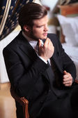 Young business man sits on vintage chair — Stok fotoğraf