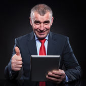 Old man working on tablet making the ok sign — Stock Photo