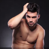 Naked young man fixes his hair — Stock Photo