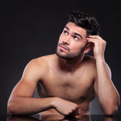 Naked young man looks up — Stock Photo